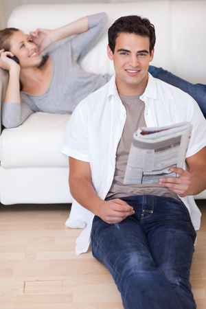 Young man leaning against the sofa with newspaper while his girlfriend listens to music photo