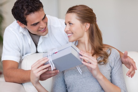 Young woman smiling happily about the present she just got from her boyfriend photo
