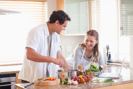 Young couple using the internet to look up recipe photo
