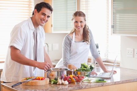Young couple using notebook to look up recipe photo