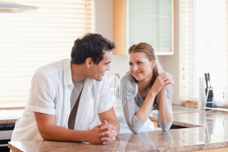 couple talking: Young couple in the kitchen looking at each other Stock Photo