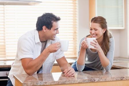 hombre tomando cafe: Pareja joven con un poco de café en la cocina Foto de archivo
