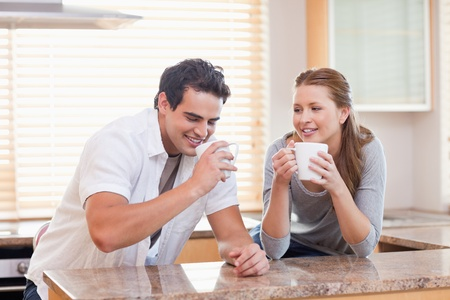 Young couple having tea in the kitchen photo