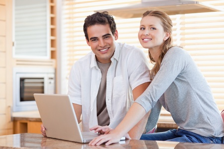 Young couple with notebook in the kitchen photo