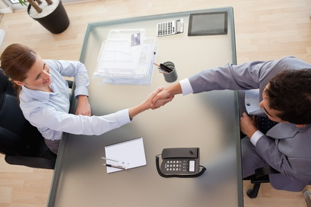 Above view of young consultant shaking hands with customer photo