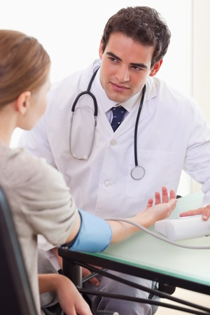 Young doctor talking to his patient about her blood pressure photo