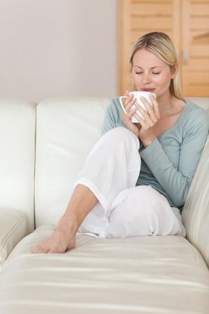 sorbo: Mujer joven en el sof� disfrutando de un sorbo de caf� Foto de archivo