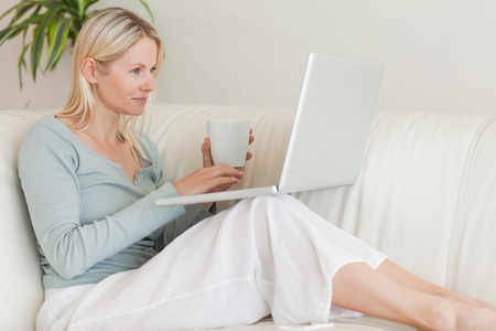 Young woman sitting on the couch with a cup of coffee and her laptop photo
