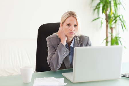 Worried businesswoman sitting behind her desk photo
