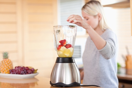 Side view of modern blender getting filled photo