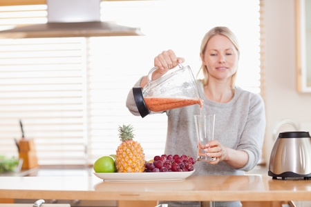 Woman pouring self made fruit juice into a glass photo