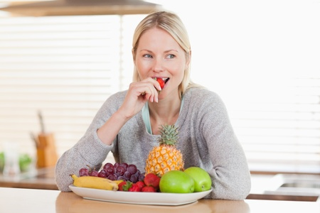 nibbling: Woman sitting in the kitchen nibbling some fruits Stock Photo
