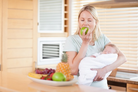 Young woman eating an apple while holding her baby Stock Photo - 11716614