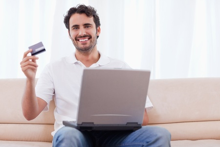 Happy man buying online in his living room photo