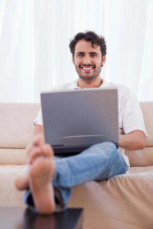 Portrait of a young man using a notebook in his living room photo