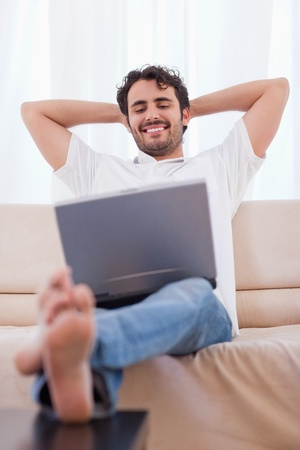 Portrait of a happy man using a laptop in his living room photo