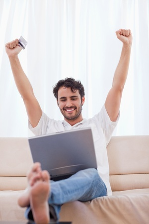 Portrait of a cheerful man shopping online in his living room photo