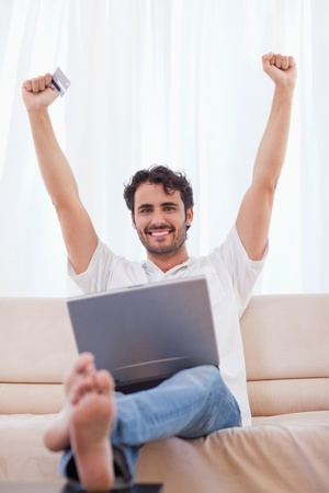 Portrait of a cheerful man buying online in his living room photo