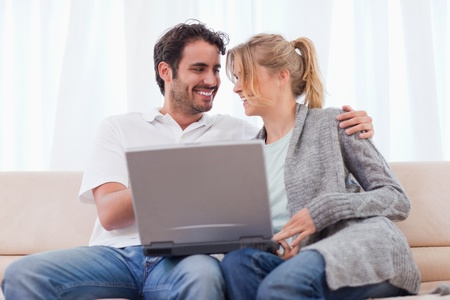 Young couple using a laptop in their living room photo