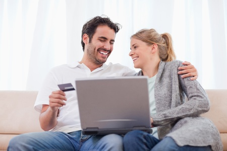 Young couple shopping online in their living room photo