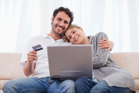 Smiling couple shopping online in their living room photo