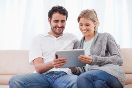 Ehefrauen: Paar mit einem Tablet-Computer in ihrem Wohnzimmer
