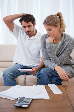 Portrait of a couple looking at their bills in their living room photo