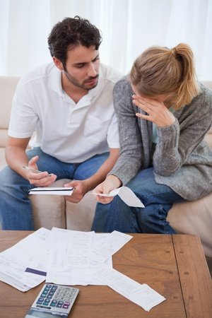 Portrait of a sad couple looking at their bills in their living room photo