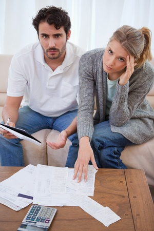 Portrait of a worried young couple looking at their bills in their living room photo