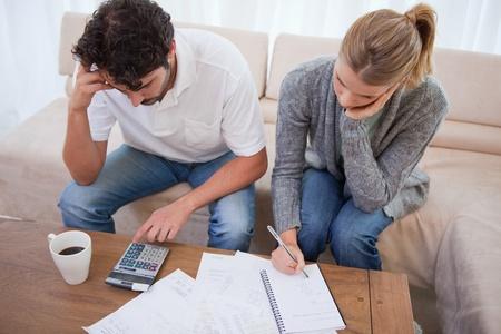 Paar sucht auf ihre Rechnungen in ihrem Wohnzimmer