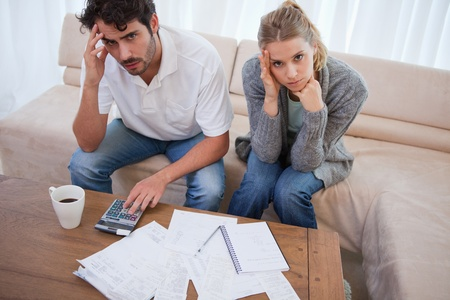 Worried couple doing their accounting in their living room photo