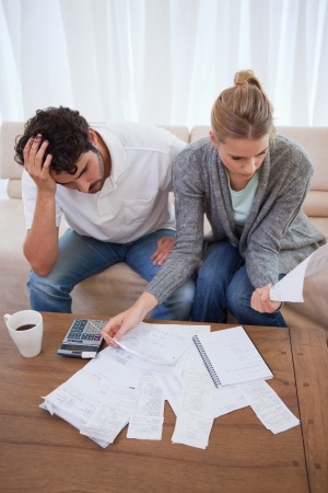 Portrait of a depressed couple doing their accounting in their living room photo