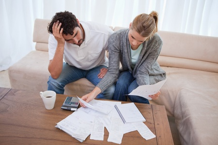 debt: Depressed couple doing their accounting in their living room