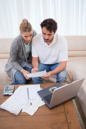 Portrait of a couple doing their accounting with a laptop in their living room photo