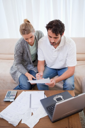 Portrait of a couple doing their accounting with a notebook in their living room photo