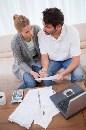 Portrait of a young couple doing their accounting with a notebook in their living room photo
