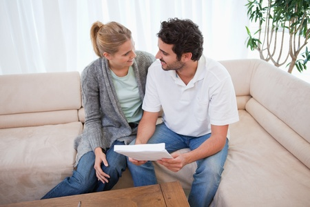 Young couple reading a letter in their living room photo