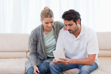 Couple opening an envelope in their living room photo