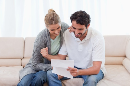 Cheerful couple reading a letter in their living room photo