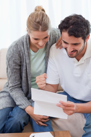 Portrait of a delighted couple reading a letter in their living room photo