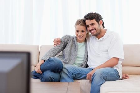 Gl�ckliches Paar vor dem Fernseher in ihrem Wohnzimmer