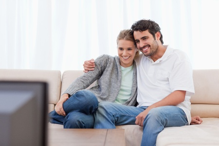 Happy couple watching TV in their living room photo