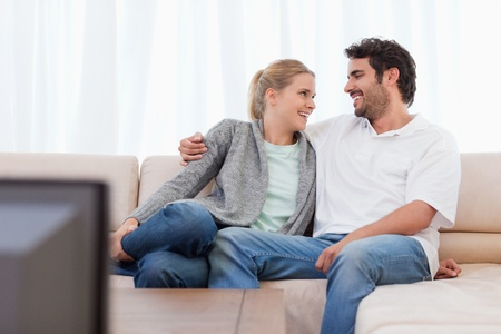 Smiling couple watching TV in their living room photo