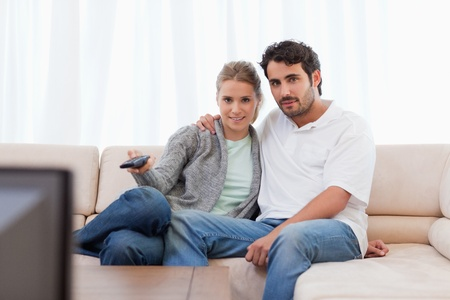 Lovely couple watching TV in their living room Stock Photo - 11684207
