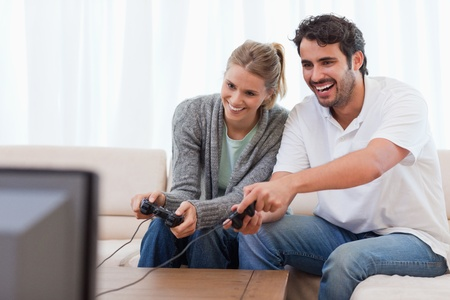 controller: Couple playing video games in their living room Stock Photo