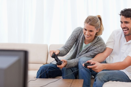 Laughing couple playing video games in their living room photo