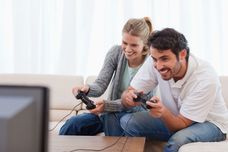 Cheerful couple playing video games in their living room photo