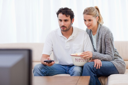 looking at watch: Couple watching TV while eating popcorn in their living room Stock Photo
