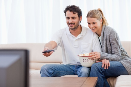 Smiling couple watching TV while eating popcorn in their living room Stock Photo - 11682917