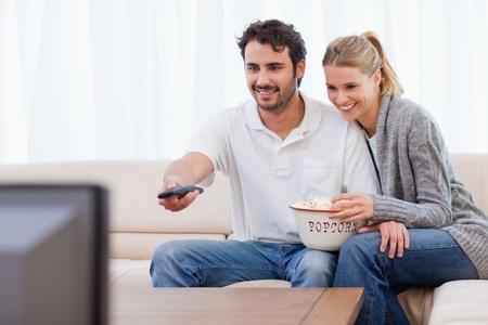 pareja viendo tv: Sonriente pareja viendo la televisi�n mientras come palomitas de ma�z en su sala de estar